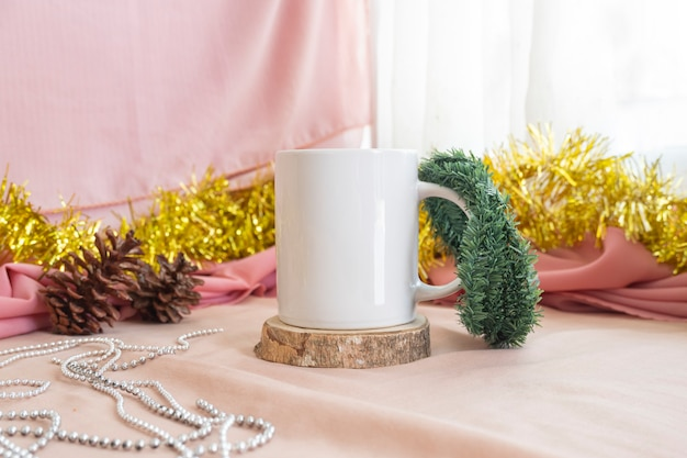 クリスマスと新年のミニマリストのコンセプト。製品マグをフィーチャーした構成。クリスマスと新年の装飾が施された木のマグカップ