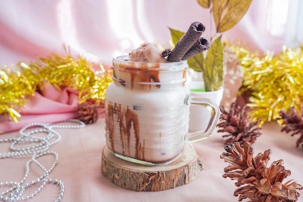크리스마스와 새해의 미니멀리즘 컨셉입니다. 컴포지션은 제품을 표시합니다. 크리스마스와 새해 장식으로 나무에 초콜릿 아이스 우유 음료