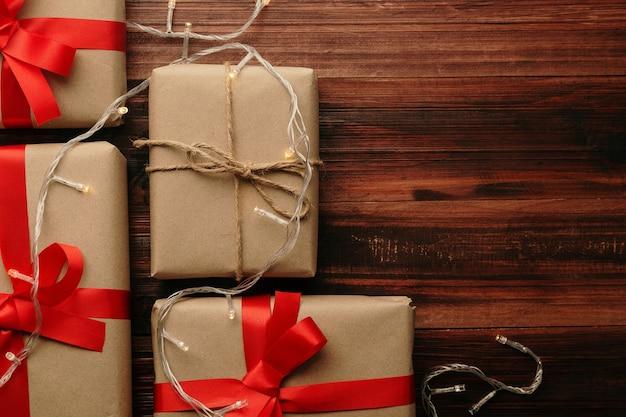 Рождество и новый год с подарочными коробками и украшением из струнных светильников на деревянном столе