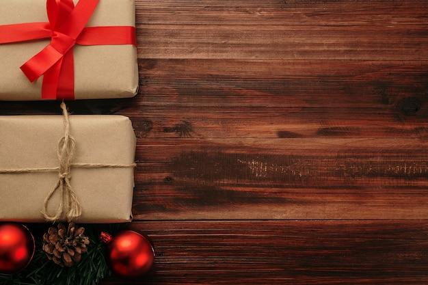 Рождество и новый год с подарочными коробками, красными шарами и украшением из шишки на деревянном столе, вид сверху фона с копией пространства.