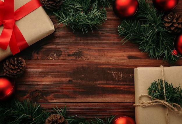 クリスマスと新年のギフトボックス、赤いボールと松ぼっくりの装飾が木製のテーブルの背景にコピースペースで上面図。