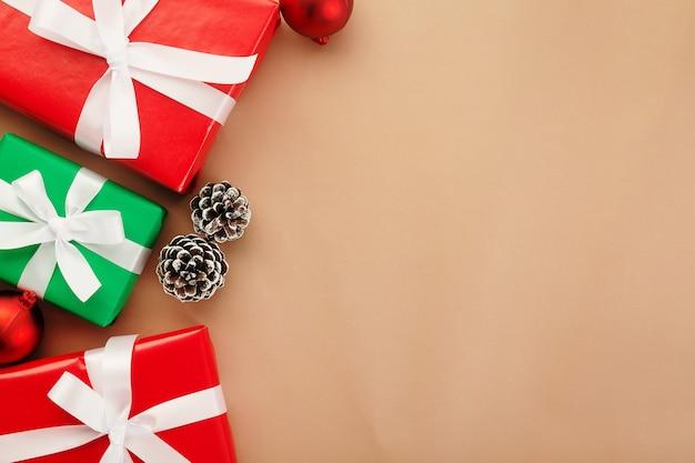 クリスマスと新年、ギフトボックス、赤いボール、ベージュの背景にスノーパインコーンの装飾、コピースペース付きの上面図。