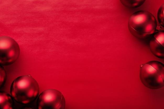 Рождество и новый год с красными шарами на красном фоне вид сверху с копией пространства.