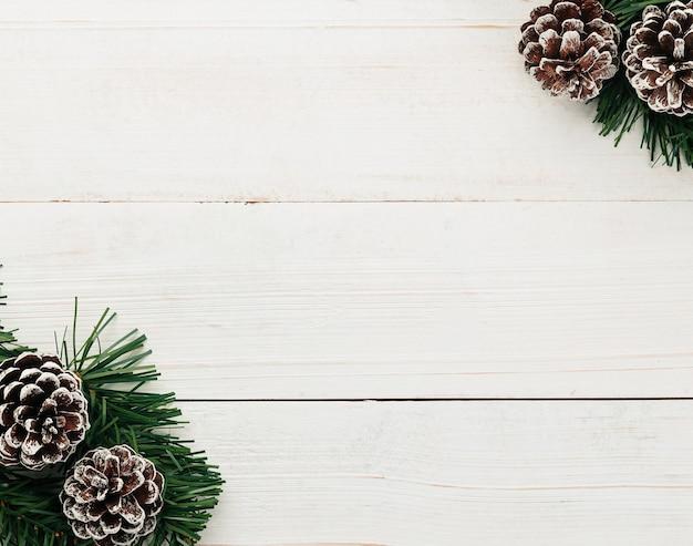 크리스마스와 새 해 복사 공간 흰색 나무 테이블 배경 평면도에 눈 소나무 콘 장식.