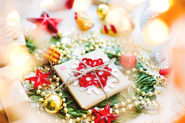 Рождество и новый год с туя филиал, украшения и подарки, завернутые в крафт-бумаги со снежинками.