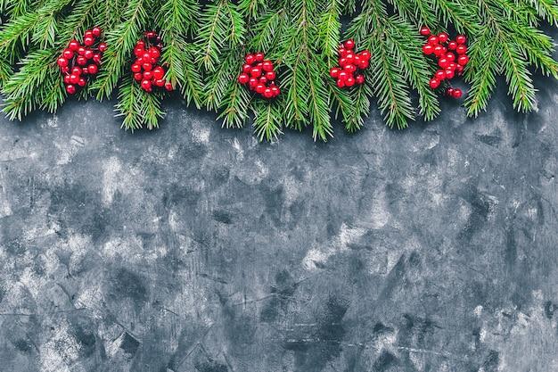 Рождество и новый год с зимними ягодами и еловыми ветками в темном стиле.