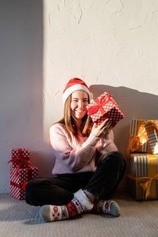 Рождество и новый год молодая женщина в новогодней шапке в окружении подарков