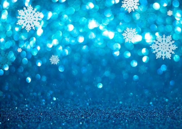 雪片とクリスマスと年末年始の青いボケ味の背景。