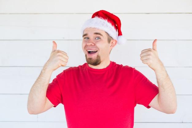 クリスマスと人々の概念-白いスペースに親指を表示するクリスマスの帽子の陽気な若い男。