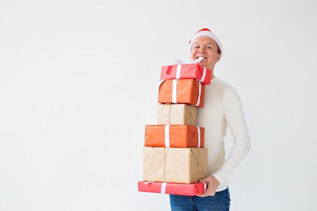 Концепция рождества и подарков - мужчина в шляпе санта-клауса держит много подарков на белом
