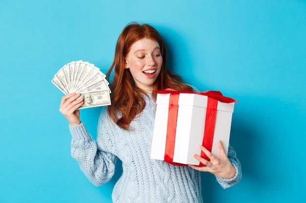 크리스마스와 쇼핑 개념. 빨간 머리, 돈과 큰 새 해 선물을 들고, 행복 하 게 웃 고, 파란색 배경 위에 서있는 명랑 소녀.