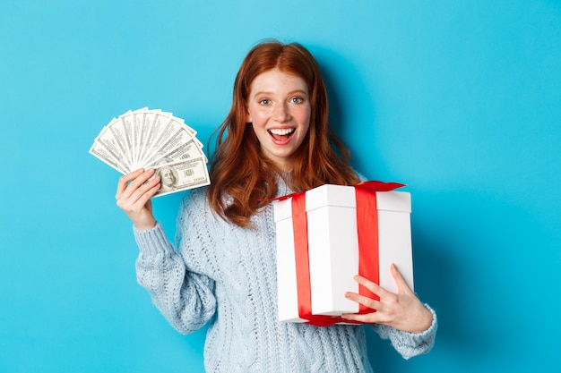 크리스마스와 쇼핑 개념. 행복 한 빨간 머리 여자 돈과 큰 크리스마스 선물을 들고, 달러와 선물을 보여주는, 기쁘게 웃 고, 파란색 배경 위에 서. 프리미엄 사진