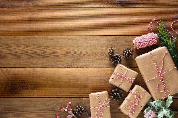 크리스마스와 겨울 방학을 조롱하십시오. 소나무 콘, 전나무 brances, 갈색 나무 테이블 복사 공간 cchristmas 선물 상자. 크리스마스 플랫 누워, 복사 공간.