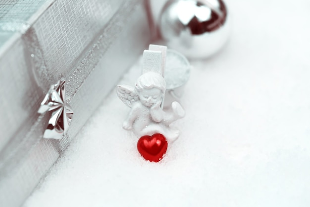 Christmas angel with a heart box with a gift selective snow soft focus