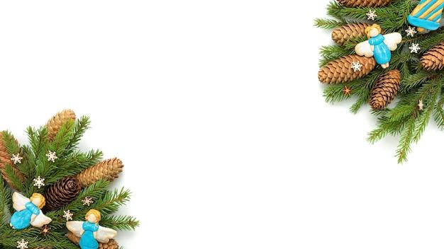 Рождественские ангелы и еловые ветки на белом фоне.