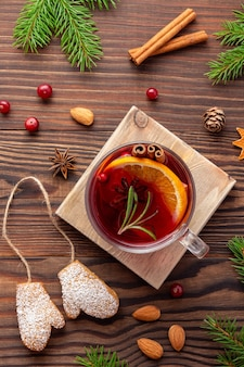 Christmas aroma composition with spruce branches and spices and gingerbread and cup of tea on wood