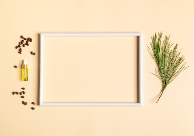 Christmas aromatherapy and spa concept with white empty frame and small glass bottle with coniferous spa aromatic essential cedar oil, branch, nuts. view from above, copy space inside frame.