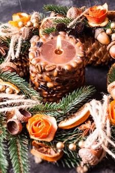 Рождественский ароматный эко-венок, украшенный кожурой мандариновых роз с зажженной кофейной свечой