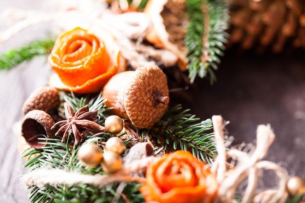 Рождественский ароматный эко-венок с сухими звездочками апельсина и аниса, украшенными розами из кожуры мандарина, деталями крупным планом