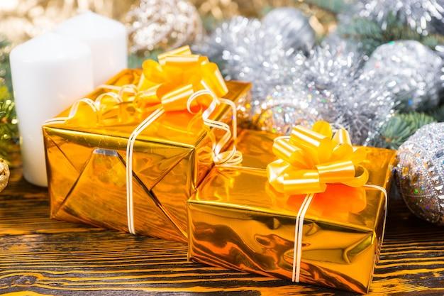 Новогодняя композиция с двумя подарочными коробками, завернутыми в блестящую золотую бумагу, белыми свечами и сосновой веткой, украшенной серебряными шарами и мишурой, на коричневом деревянном столе