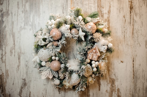 Christmas artificial wreath with white and rosa color ornaments, balls, tapes and flowers