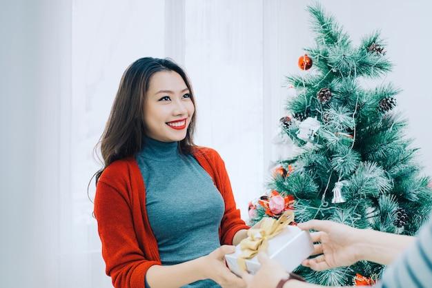 クリスマスアジアのカップル。彼女のガールフレンド/妻に新年の人々を祝う家で贈り物を与えるハンサムな男