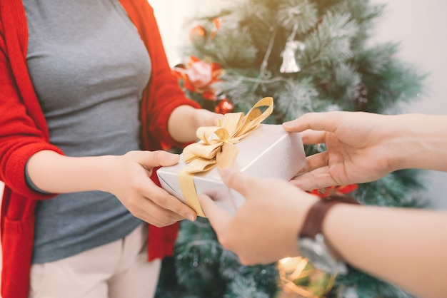 Рождественские азиатские пары. красивый мужчина делает подарок своей девушке / жене дома во время празднования нового года.