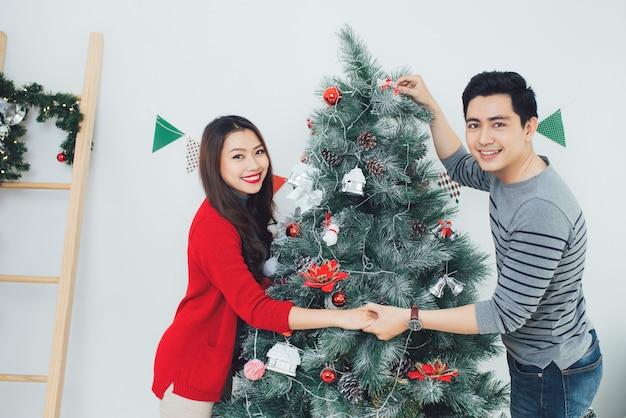 Рождество азиатских couple.happy улыбается семья дома празднует. новогодние люди