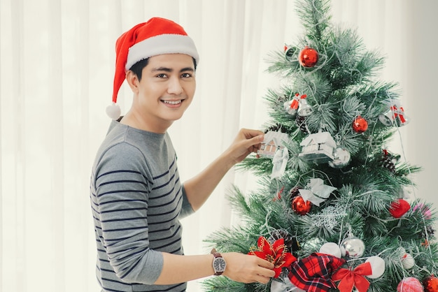 Рождество. азиатский красавец стоя новое рождественское дерево дома празднуя новый год.