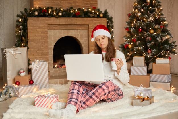 집에서 크리스마스, 검역 기간 동안 겨울 휴가를 축하하고 슬픈 표정을 가진 아가씨는 무릎에 노트북을 들고 바닥에 앉아 커피 또는 차를 마시고 컵을 손에 들고 있습니다.