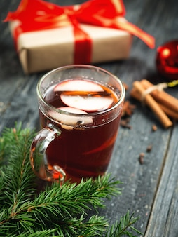 Christmas atmosphere. gift box and a glass of mulled wine