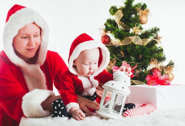 孤立したモミの木の下のクリスマスの赤ちゃんとお母さん