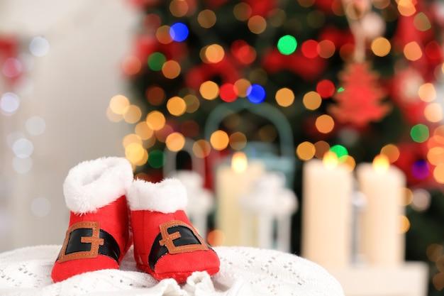 ぼやけた背景に対してニット生地のクリスマスのベビーブーツ
