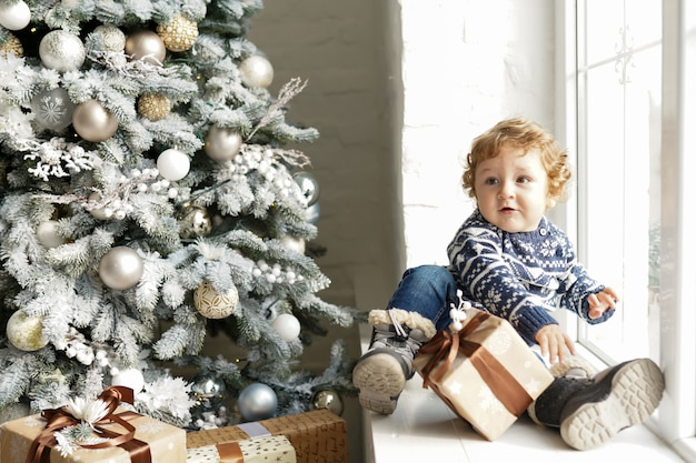 Christmas baby , child holding gift box sitting near christmas tree on the sofa at home