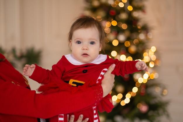 クリスマスツリーの近くのサンタの衣装でクリスマスの赤ちゃん。メリークリスマス、そしてハッピーニューイヤー。