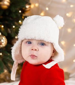カメラを見ているクリスマスの赤ちゃん。赤いドレスと白い帽子のかわいい女の子は感情を表現します。小さな子供とクリスマスのコンセプト