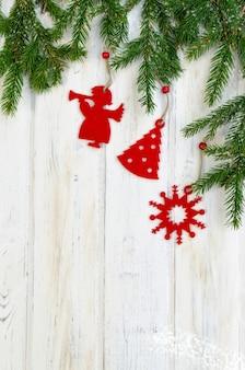 雪で覆われた装飾とモミの木の枝とのクリスマスの背景