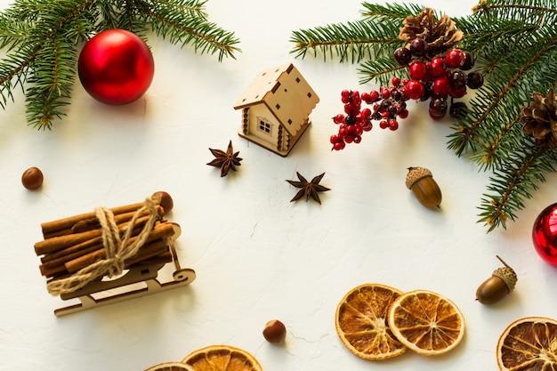 전통적인 새해의 유기농 재료인 말린 오렌지, 계피, 아니스 별, 나무 장난감 조각으로 구성된 크리스마스 배경입니다.