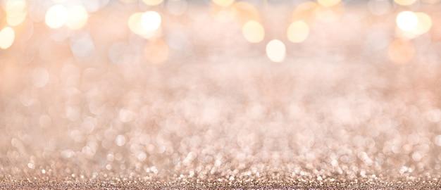 クリスマスの背景。焦点がぼけたキラキラ、点滅する星とライトの抽象的なゴールドホリデーパノラマ背景。ぼやけたボケ