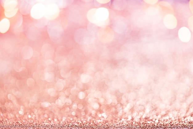 クリスマスの背景。焦点がぼけたキラキラ、点滅する星とライトで抽象的なピンクのローズゴールドの休日のパノラマの背景。ぼやけたボケ