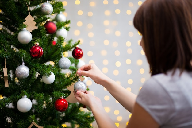 Christmas background - back view of girl decorating christmas tree at home