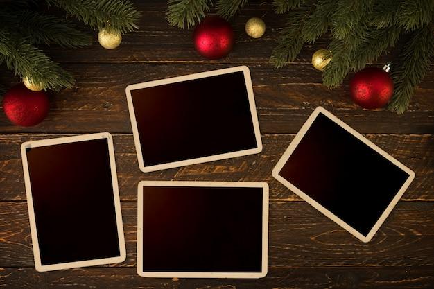 クリスマスの背景 - 空の写真フレームの紙、モミの木と木製のテーブルに素朴な要素を装飾。クリエイティブフラットレイアウトとトップビューの構図。ヴィンテージ色調
