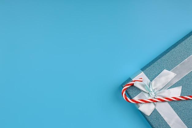 クリスマスの背景。青い背景に弓と縞模様のキャンディーと青いキラキラギフトボックス。テキスト、上面図、フラットレイ用の空のスペース
