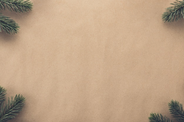 Christmas background border design with green pine at corners on brown paper
