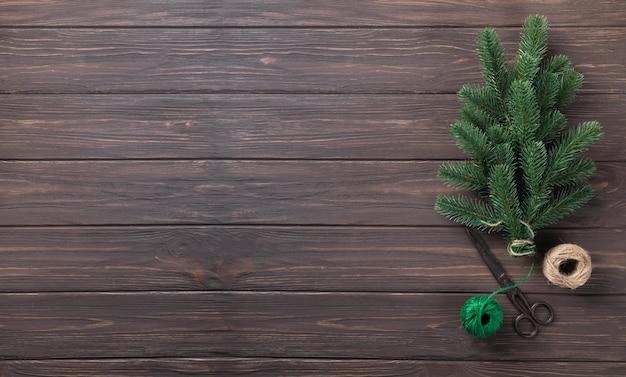 クリスマスの背景。木製のテーブルの上にひもで結ばれたモミの枝の花束。バナー。