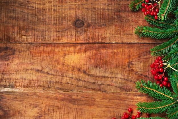 Рождественский фон. филиалы ели и красные ягоды калия на деревянном фоне. вид сверху. рождественская или новогодняя открытка. рамка. место для текста, место для копирования, плоская планировка, макет
