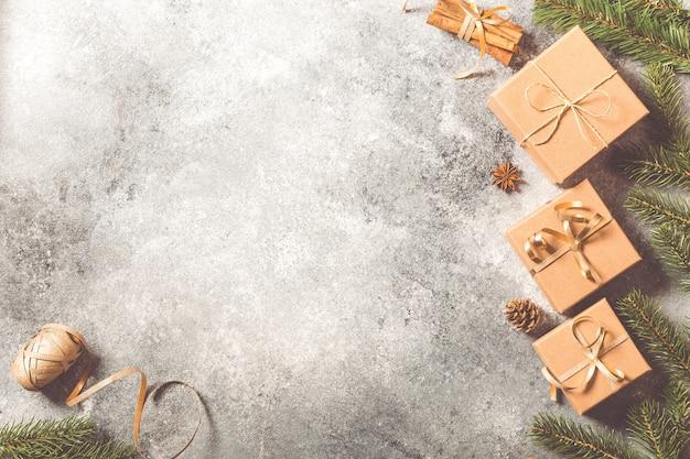 크리스마스 배경입니다. 밝은 콘크리트 배경에 전나무 가지, 선물, 과자, 계피 크리스마스 구성