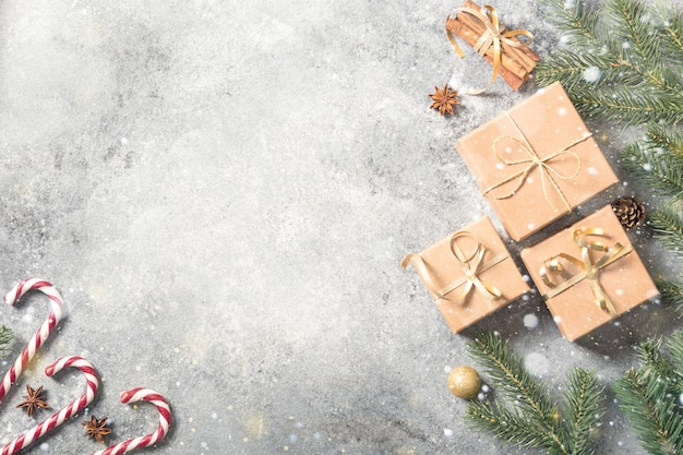 クリスマスの背景。明るいコンクリートの背景にモミの枝、ギフト、お菓子、シナモンとクリスマスの構成
