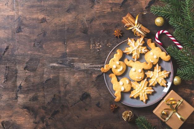 크리스마스 배경입니다. 어두운 나무 배경에 전나무 가지, 선물, 과자, 쿠키, 계피와 함께 크리스마스 구성