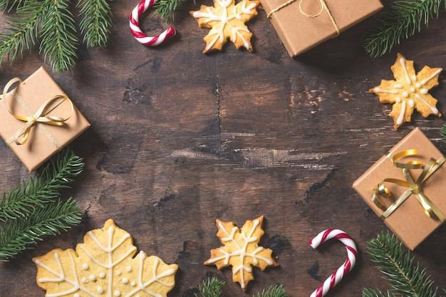 クリスマスの背景。ダークウッドの背景にモミの枝、ギフト、お菓子、クッキー、シナモンとクリスマスの構成